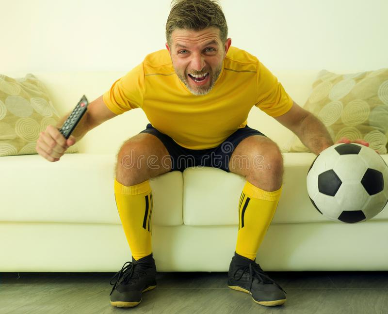 Funny and crazy soccer fan man dressed in his team uniform watching football game on television celebrating scoring goal excited. Screaming spastic and cheering stock images