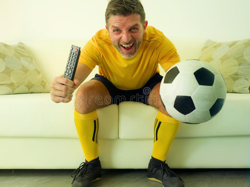 Funny and crazy soccer fan man dressed in his team uniform watching football game on television celebrating scoring goal excited. Screaming spastic and cheering royalty free stock images