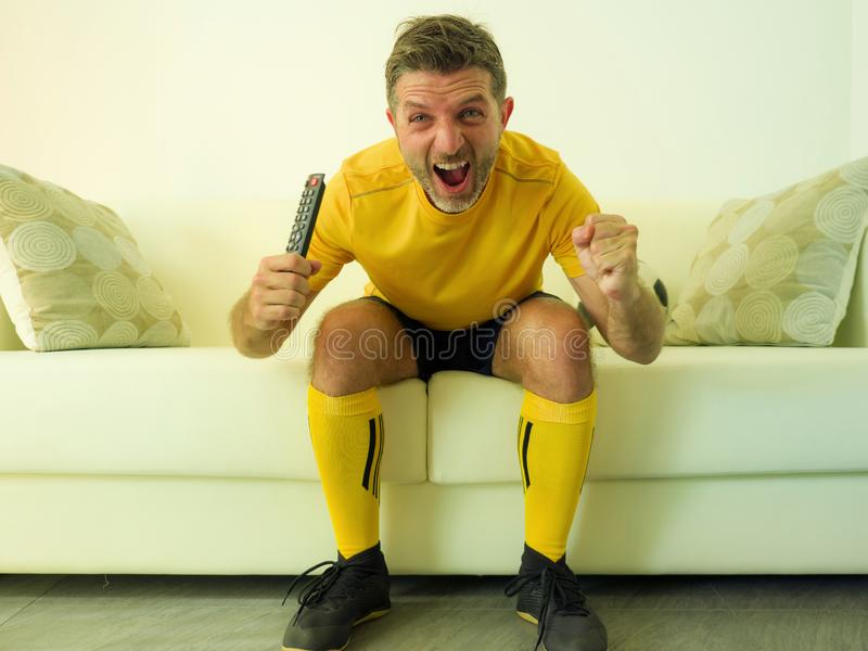 Funny and crazy soccer fan man dressed in his team uniform watching football game on television celebrating scoring goal excited. Screaming spastic and cheering royalty free stock photo