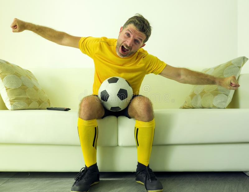 Funny and crazy soccer fan man dressed in his team uniform watching football game on television celebrating scoring goal excited. Screaming spastic and cheering royalty free stock photos