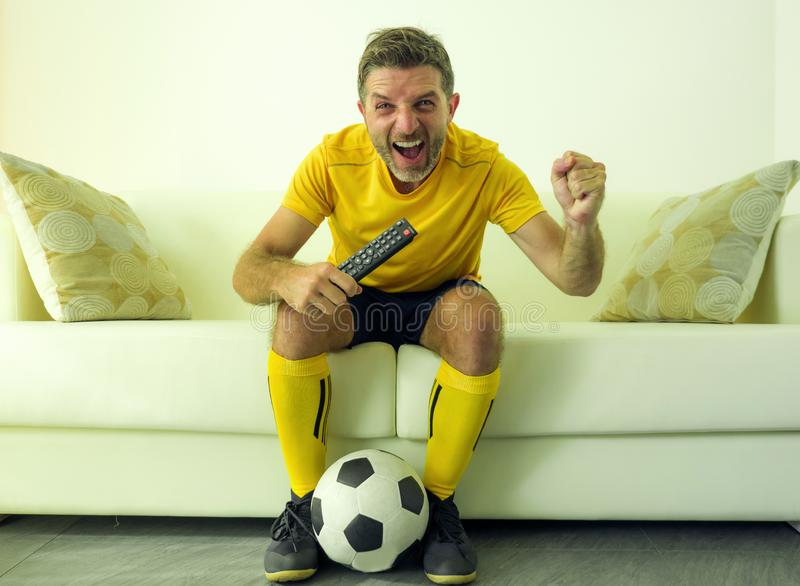 Funny and crazy soccer fan man dressed in his team uniform watching football game on television celebrating scoring goal excited. Screaming spastic and cheering stock image