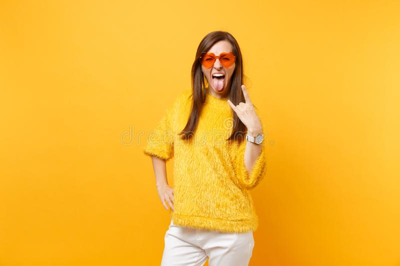 Funny crazy young woman in fur sweater and heart orange glasses screaming, showing rock-n-roll sign isolated on bright. Yellow background. People sincere royalty free stock photos