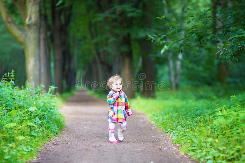 Funny curly baby girl in rain boots walking in a park stock images