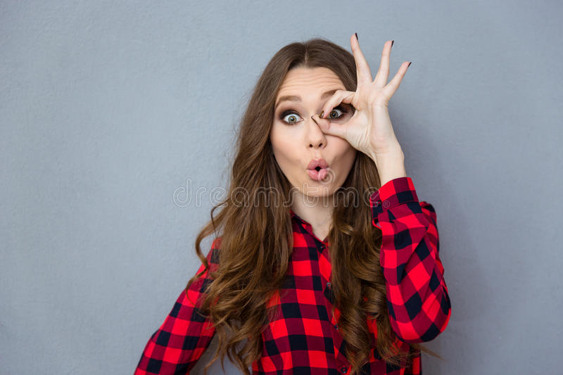 Funny curly girl showing okay gesture near her eye. Funny amusing curly girl in checkered shirt showing okay gesture near her eye royalty free stock photos