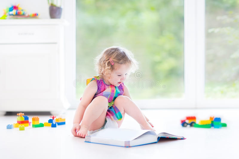 Funny curly toddler girl reading a book sitting on floor stock photos