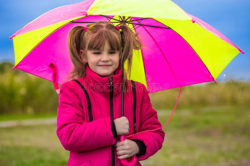 Funny cute girl with colorful umbrella playing in the garden stock images