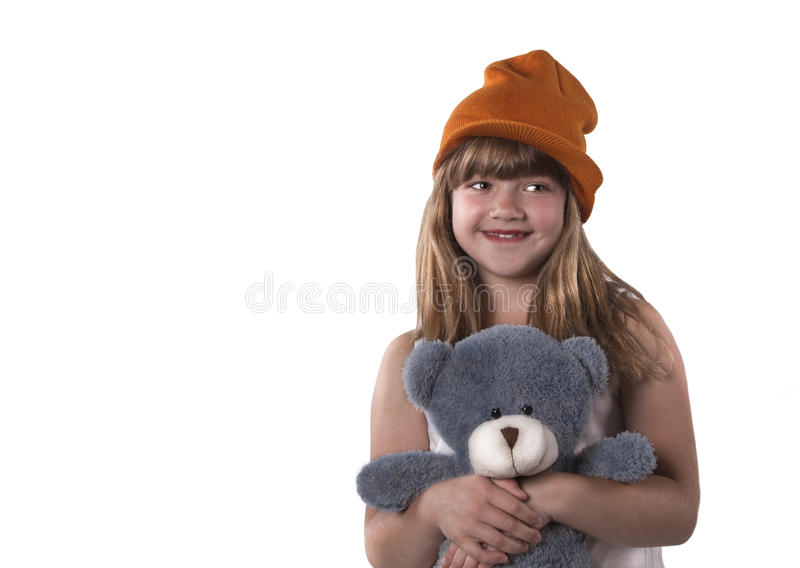 Funny cute girl with dimple on the cheeks cuddle her gray teddy. Portrait of cheerful girl with hat and teddy bear on the white background royalty free stock images