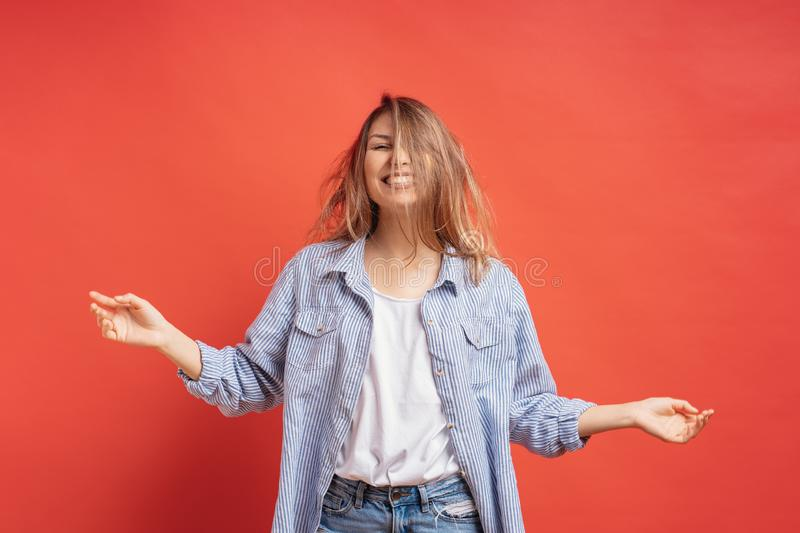 Funny, cute girl having fun while playing with hair isolated on a red background royalty free stock photos