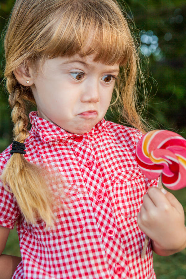 Funny cute girl surprised candy stock photo