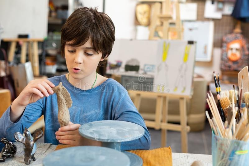 Funny cute handsome boy modeling figures out of clay royalty free stock photos