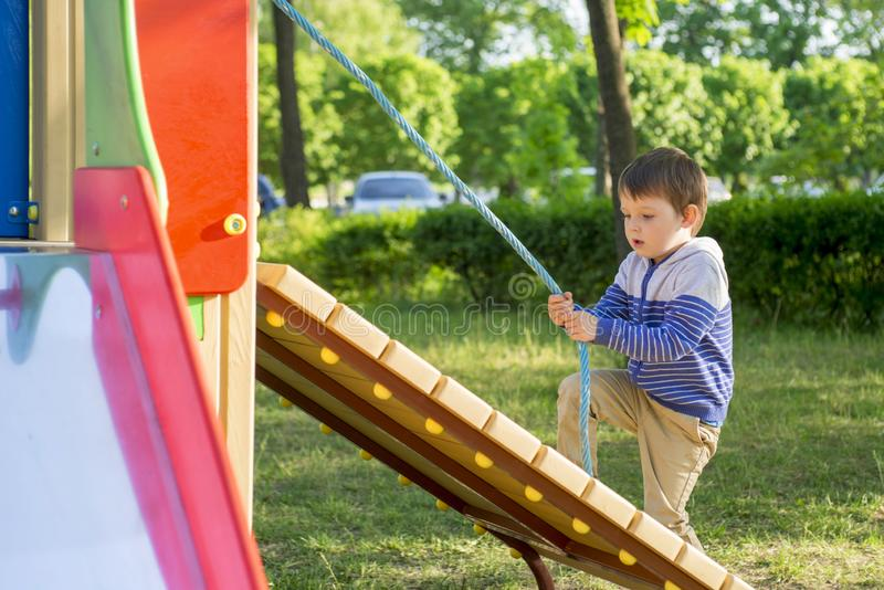 Funny cute happy baby playing on the playground. The emotion of happiness, fun, joy. Active little boy playing on playground royalty free stock image