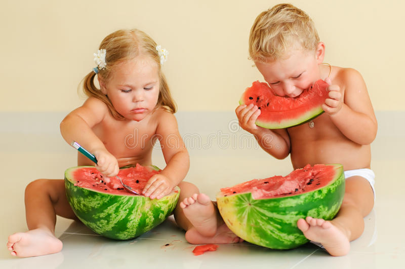 Funny cute kids eating watermelon royalty free stock image
