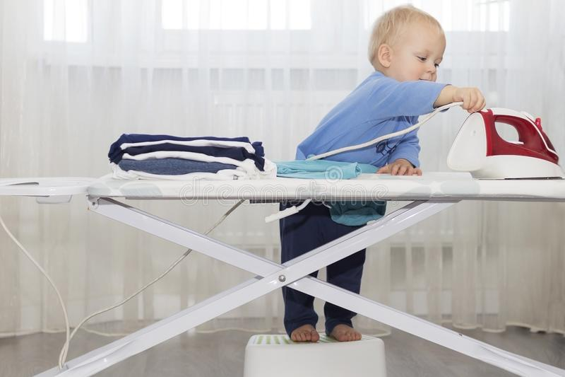 Funny cute little baby boy housekeeper ironing clothes. Kid engaged in domestic work royalty free stock photos