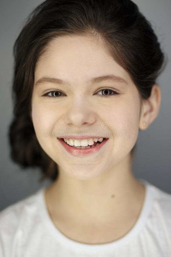 Funny cute young girl smiling winking showing tongue looking at camera over white background. stock image
