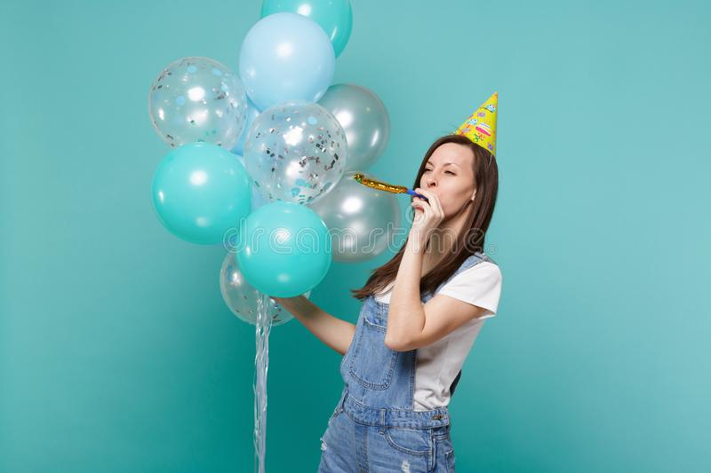 Funny cute young woman in birthday hat looking aside blowing in pipe, celebrating, holding colorful air balloons. Isolated on blue turquoise background royalty free stock photography