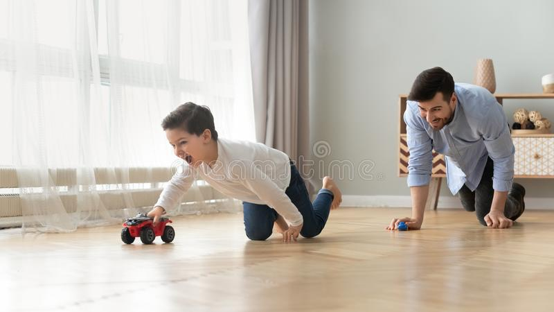 Funny dad and excited kid son racing cars at home. Funny happy male family young adult dad and cute excited little kid son pretending racing on warm wooden floor stock images