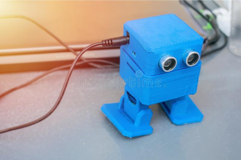 Funny dancing blue robot, printed on the 3D printer on the background of devices and cords. The robot model printed on automatic stock photo