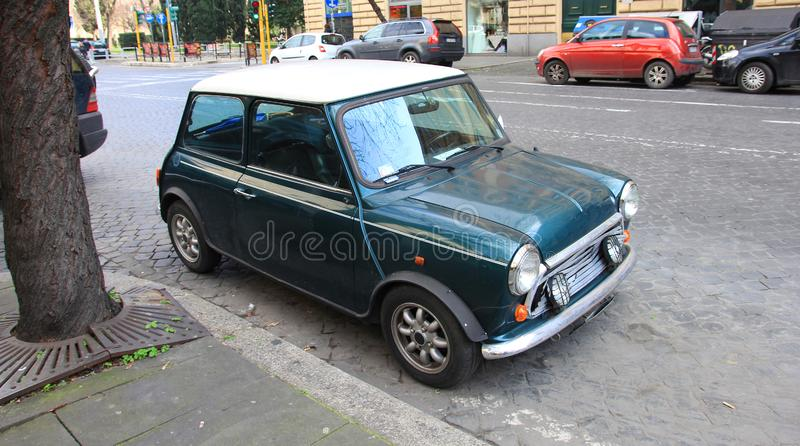Funny dark green small old little italian mini car with round headlights and green bright body and white top on roman street. Foreground stock photo