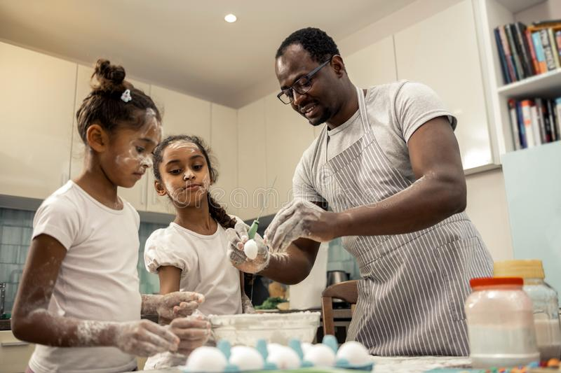 Funny dark-haired daughters cooking cupcakes with father. Cupcakes with father. Funny dark-haired daughters cooking cupcakes with father wearing striped apron royalty free stock photo