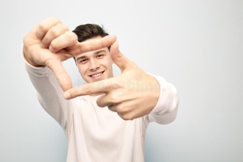 Funny dark-haired guy dressed in a white long sleeve t-shirt stands and keeps his hands in front of him making with stock photos