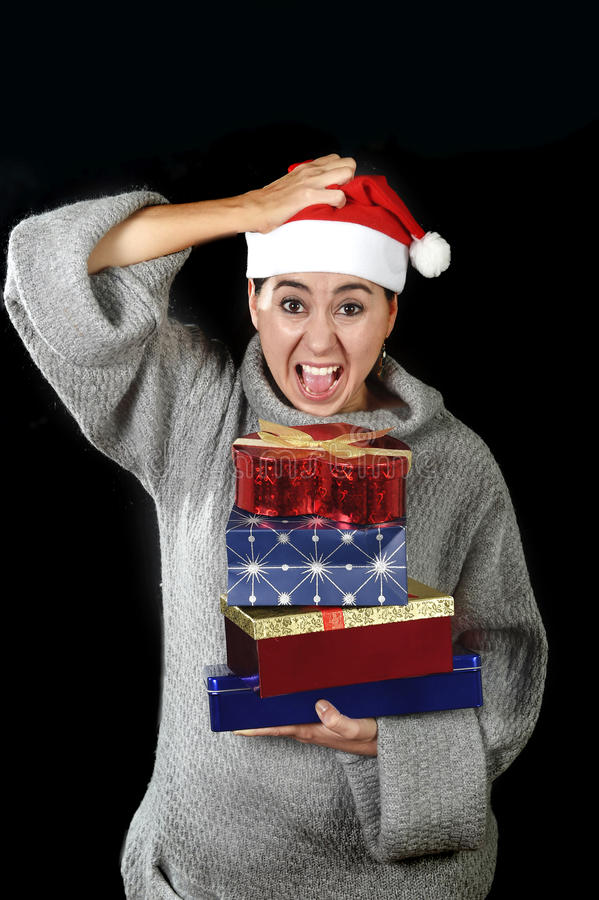 Funny desperate woman in Santa Christmas hat in stress about December gifts and presents shopping screaming. Holding xmas packets pile isolated on black royalty free stock photos