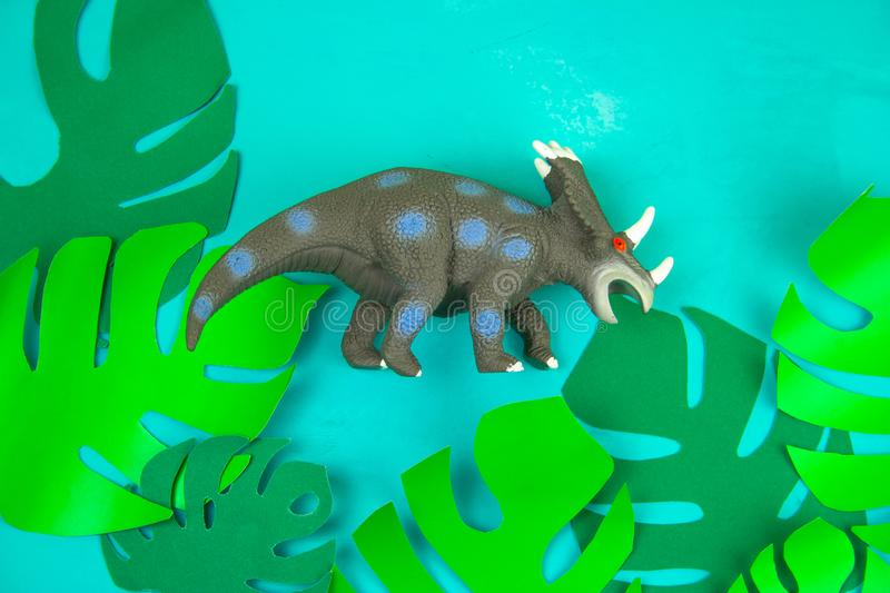 Dinosaur toy on blue background with green paper cut tropical leaves. Funny dinosaur toy on blue background with green paper cut tropical leaves royalty free stock photos