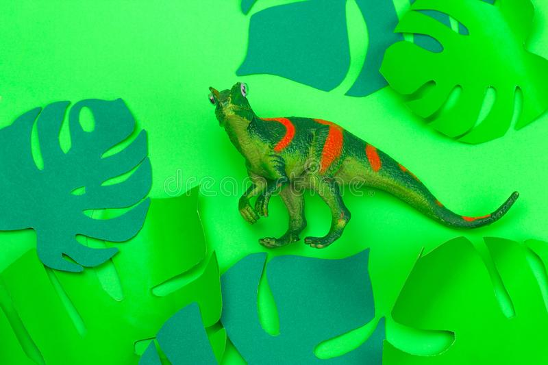 Dinosaur toy on green background with green paper cut tropical leaves stock photo