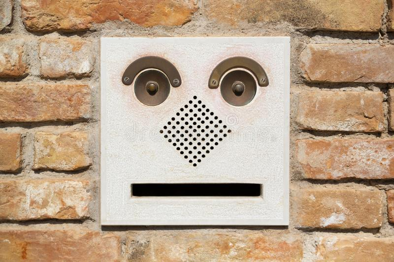 A funny doorbell panel on old brick wall and mail post box with letter. Fake face concept royalty free stock photo