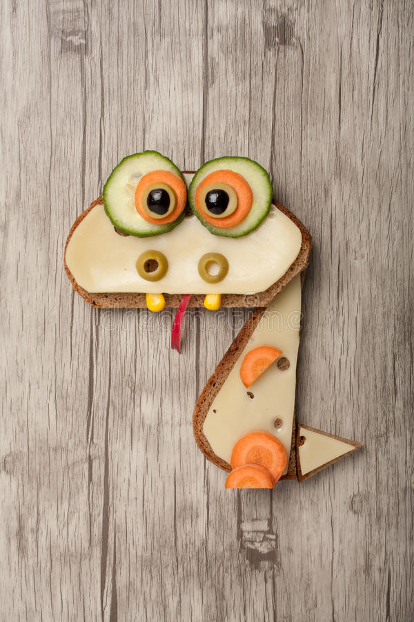 Funny dragon made of bread and cheese stock photo