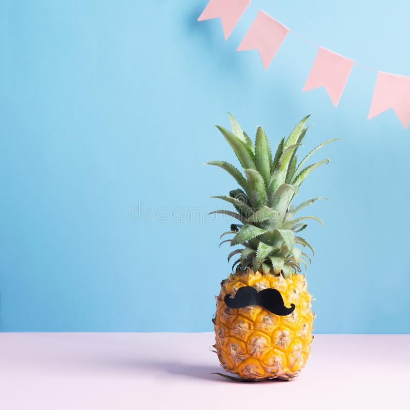 Funny dressed up pineapple with a black mustache on a pastel blue background with festive pink flags. Minimalism. Art. stock photos