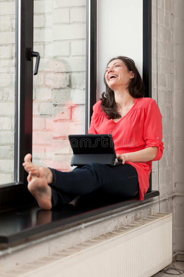 Funny e-mail. Girl on windowsill 've got funny e-mail and laughing out loud stock images