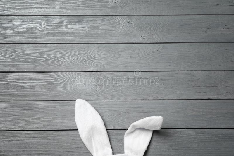 Funny Easter bunny ears on wooden background, top view. With space for text royalty free stock photo