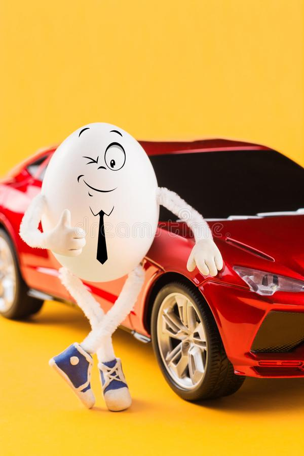 Easter egg businessman standing near red car royalty free stock photo