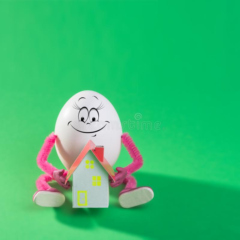 Funny easter egg girl holding miniature paper house royalty free stock photo