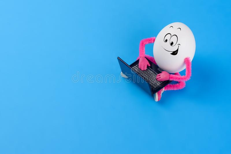Funny Easter egg working on a notebook computer royalty free stock photo