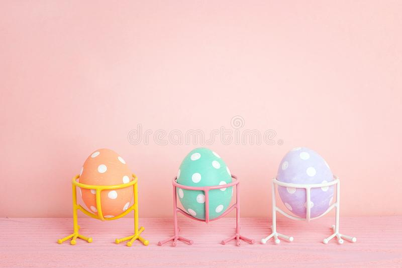 Funny Easter eggs on bird legs on pink background. stock photo