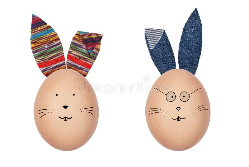 Funny Easter eggs decorated with textile ears. Bunny faces drawn on the eggs. Creative Easter decoration. stock image