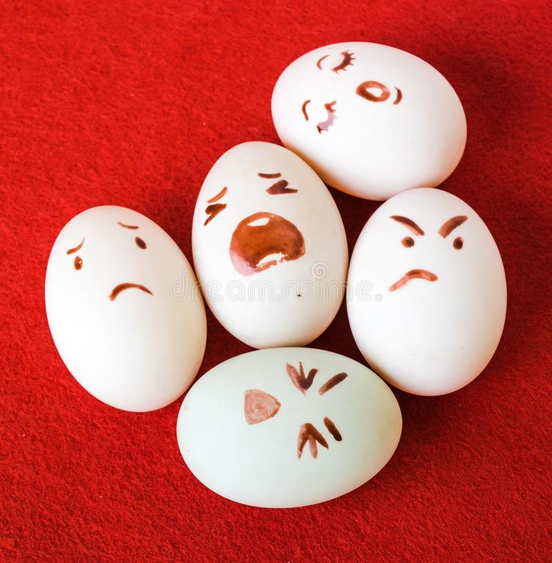 Funny Easter eggs with different emotions on his face. Funny easter emotion eggs on red stock photography