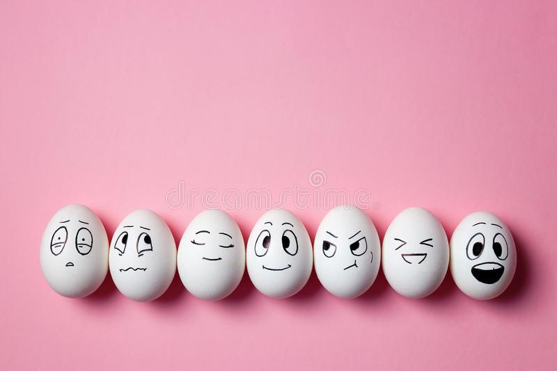 Funny Easter eggs with facial expressions. Eggs with different faces on pink background stock photos
