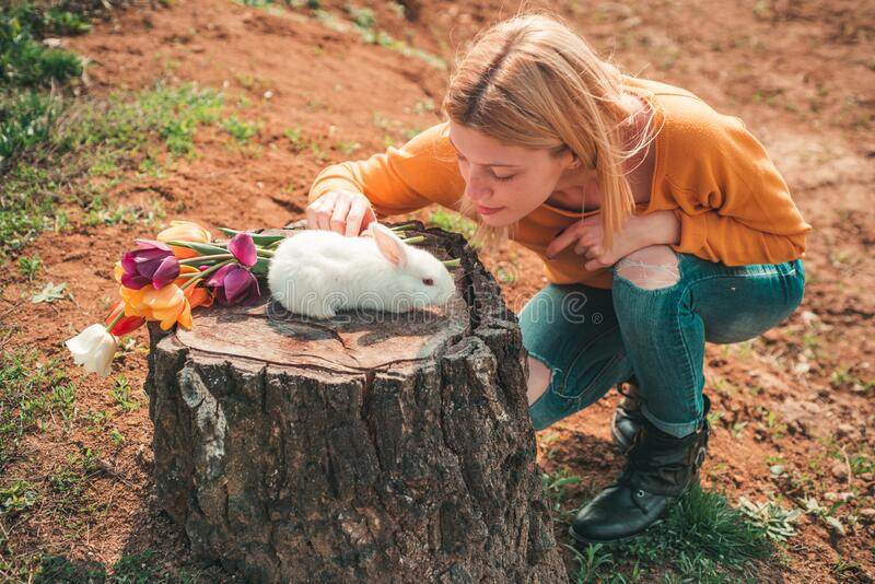 Funny Easter rabbit. Little girl having fun on Easter egg hunt. Happy smiling little teen girl with bunny hunting easter royalty free stock photo