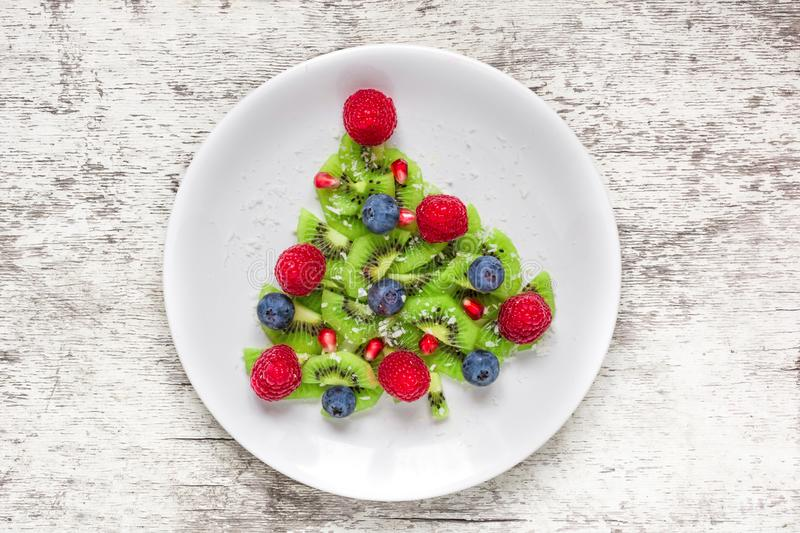 Funny edible christmas tree made from fruits and berries. Christmas breakfast idea for kids stock photos