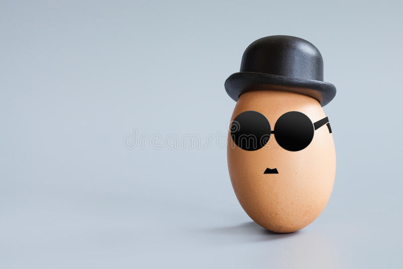 Funny egg face with black glasses and retro hat. Old fashion character for Easter holiday greeting card. Macro view, gray background copy space royalty free stock photos