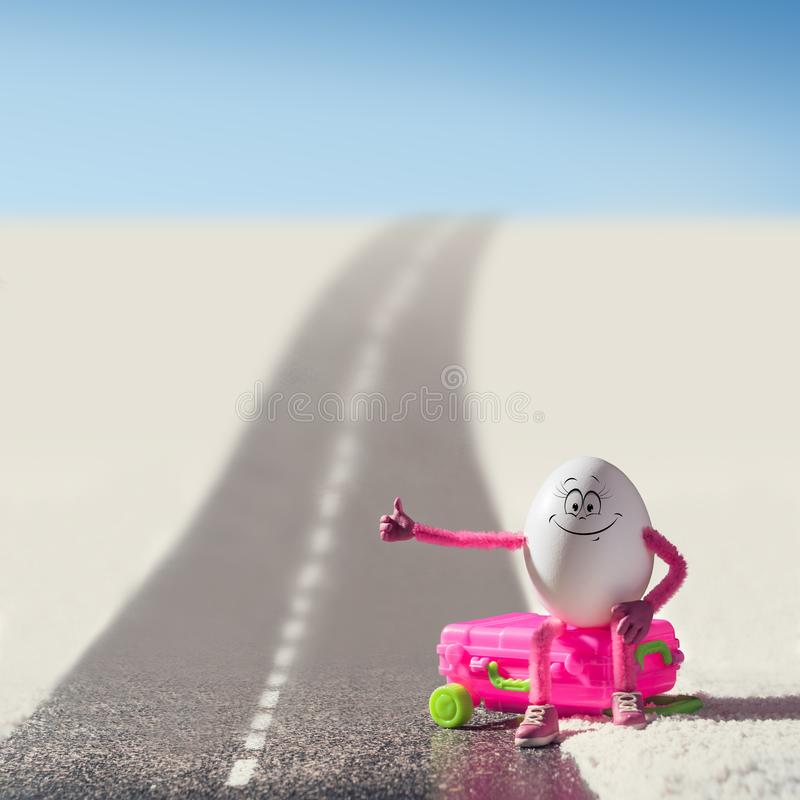Funny egg girl hitchhiking. On a road in a desert. Travel concept stock image