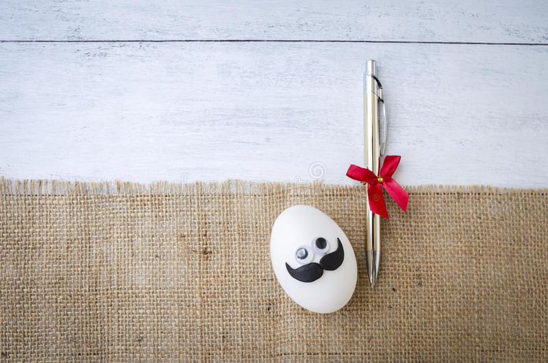 Funny egg with pen gift on hessian fabric. Father`s day concept background, funny egg with pen gift on hessian fabric over white wood background stock photo