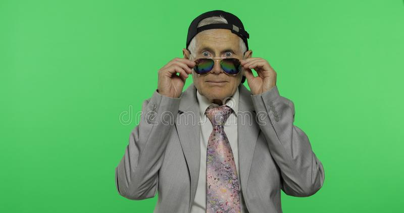 Funny elderly businessman in sunglasses and cap. Old man winks stock images