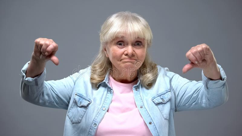 Funny elderly female showing thumbs-down gesture, unhappy with state government stock photo