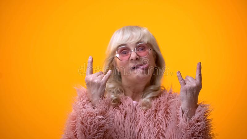 Funny elderly woman in pink coat making rocker gestures and showing tongue, fun stock images