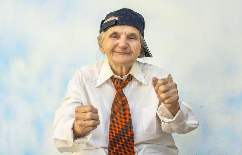 Funny elderly woman supporting something. stock image
