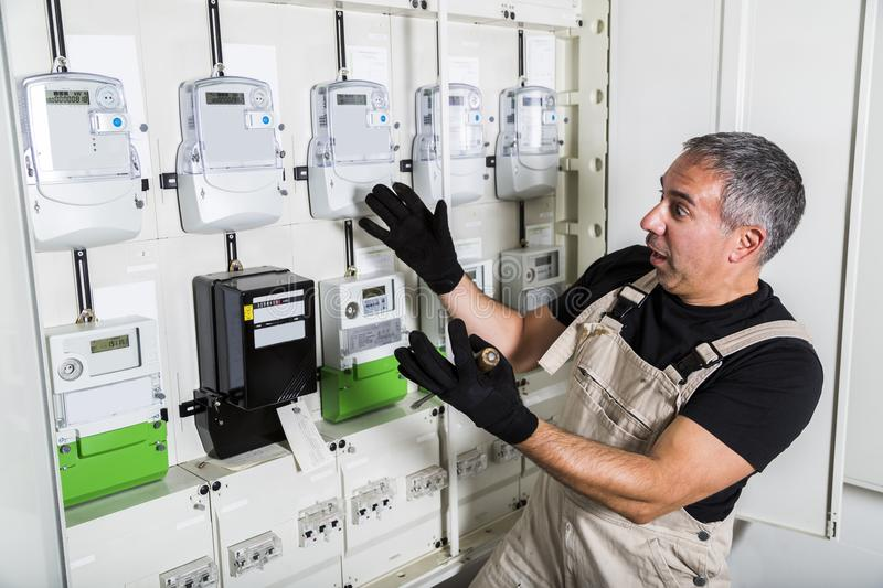 Funny electrician doing electrical repair in switchboard royalty free stock images