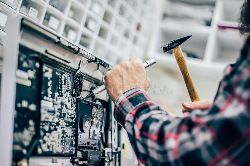 Funny electrician engineer repair computer monitor with hammer and screwdriver. Funny electrician engineer repair faulty electric in computer monitor with hammer stock image